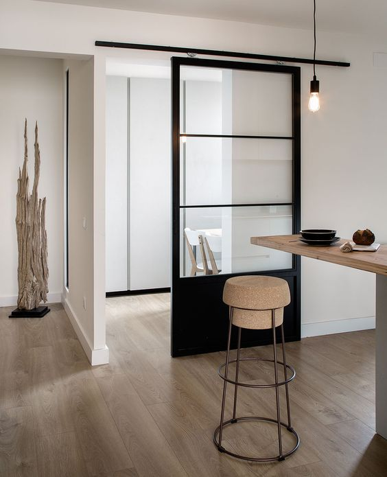 a minimalist home with a matching minimalist black frame metal sliding door that separates the spaces well enough and still rpovides both of them with light