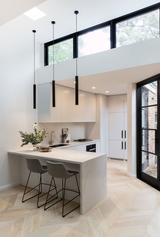 a minimalist space in black and white, with minimalist furniture and black pendant lamps plus a clerestory window over the space