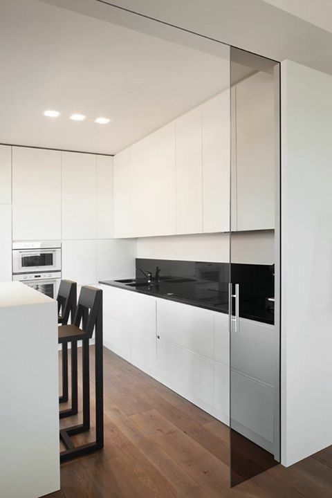 a minimalist white kitchen separated with dark glass doors that echo with the countertops and the backsplash and look modern and edgy
