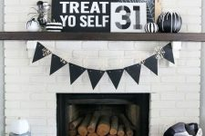 a modern Halloween fireplace clad with white brick, with black signs and artworks, black and white pumpkins and spiders is very stylish