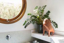 a modern bathroom with a porthole window, a bathtub clad with tiles, a stone shelf and potted greenery is a cool idea