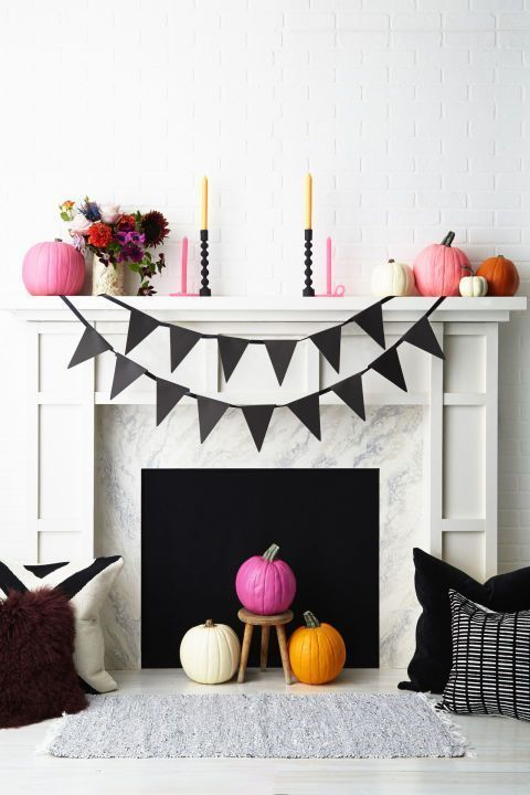 a modern bright Halloween fireplace with a black bunting, colorful pumpkins, bold blooms and candles plus graphic pillows