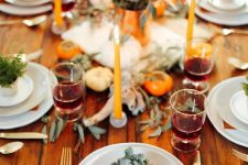 a modern bright rustic Thanksgiving tablescape with bold blooms, eucalyptus, rust-colored napkins, orange candles is very cool