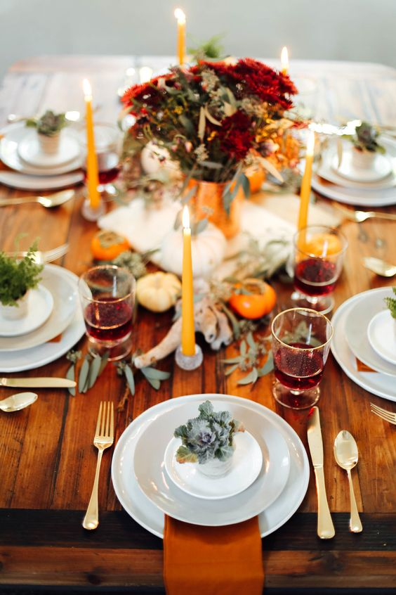 a modern bright rustic Thanksgiving tablescape with bold blooms, eucalyptus, rust colored napkins, orange candles is very cool