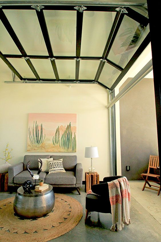 a modern desert-styled living room with a garage door that opens it up to a private courtyard or a litte terrace for fresh air