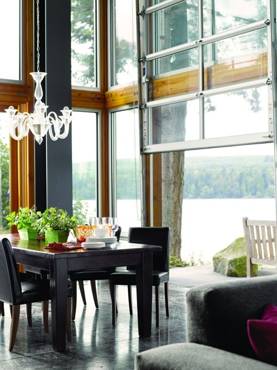 a modern dining room with dark furniture, glazed walls and a garage door that opens up the space to the lake outdoors is amazing