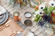 a modern farmhouse Thanksgiving tablescape with a plaid runner, neutral napkins, neutral and bold blooms and copper touches
