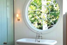 a modern farmhouse bathroom with a large porthole window next to the tub to fill the space with natural light