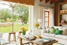 a modern farmhouse living room with wooden beams, neutral seating furniture, a wooden coffee table and colorful pillows