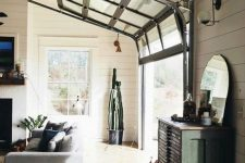 a modern farmhouse neutral space and a black framed garage door that opens up the space to the outdoors