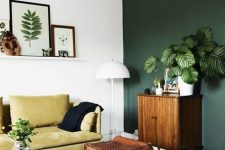 a modern living room with a dark green accent wall, a mustard sofa, a stained cabinet, a brown woven pouf and a ledge gallery wall
