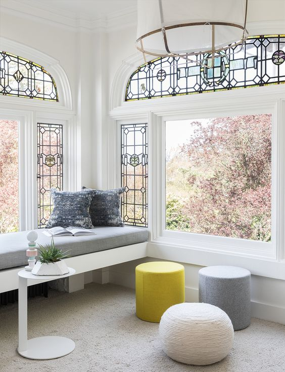 a modern living room with large dinwos with stained glass, a built-in couch, poufs and a small table plus gorgeous views of bloomign trees