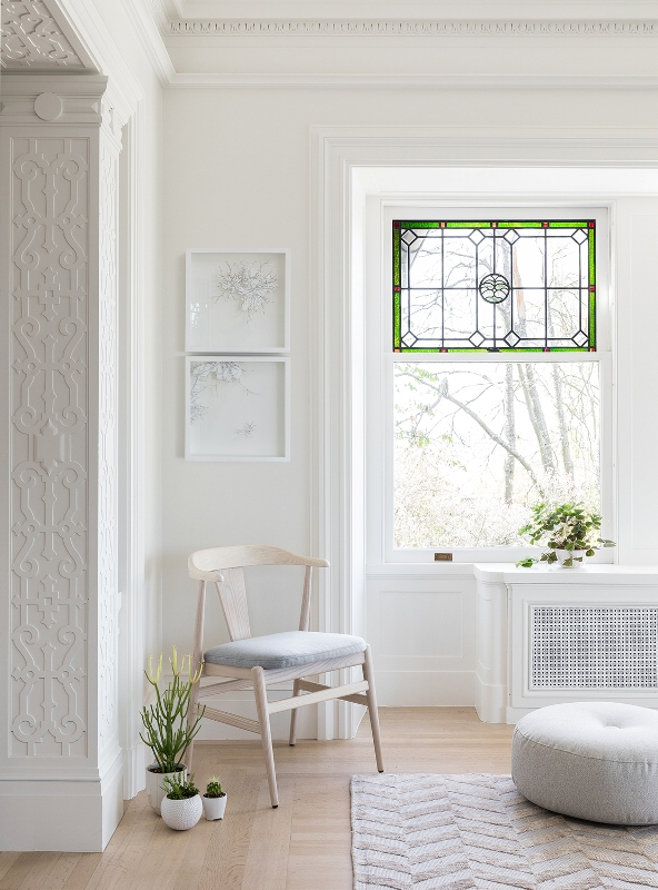 a modern neutral space with a stained glass window, simple furniture and art and some potted plants is a very cool and fresh idea