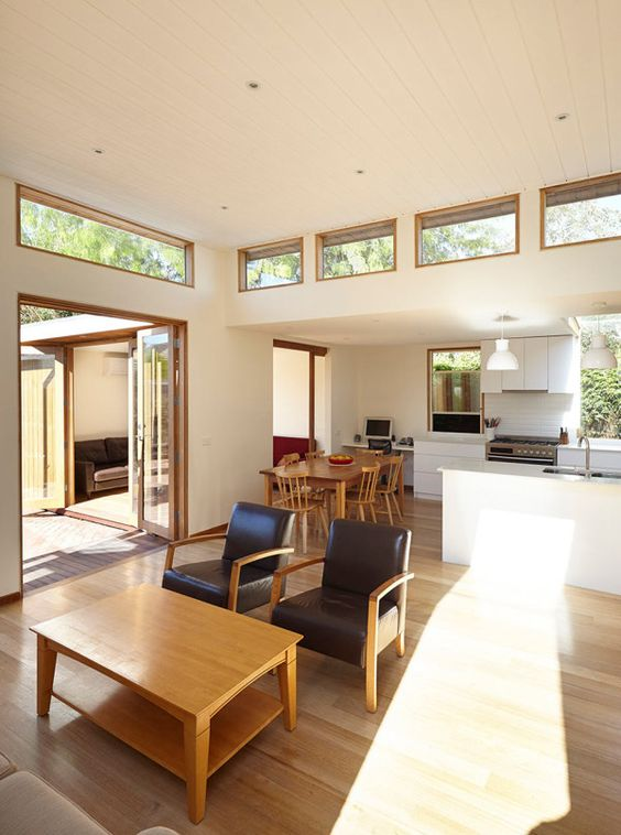 a modern open layout with a neutral color palette, with clerestory windows dotting the facade and giving more light to the spaces