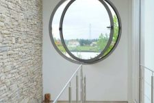 a modern porthole window in the staircase space is a cool way to add light and create an illusion of more space