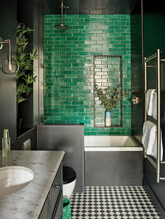 a moody bathroom with a green tile accent wall, a tub clad with black tiles, a black and white tiled floor, a black vanity and some greenery