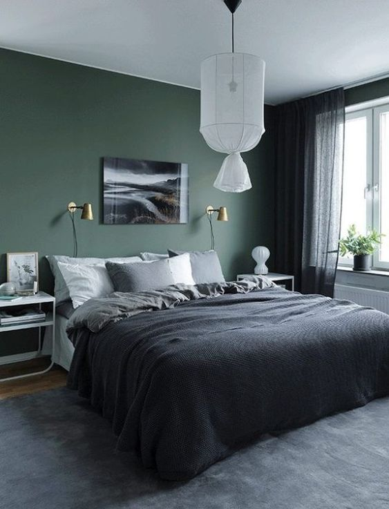 a moody bedroom with a dark green accent wall, an upholstered bed with dark bedding, white nightstands, a pendant lamp and black sheer curtains