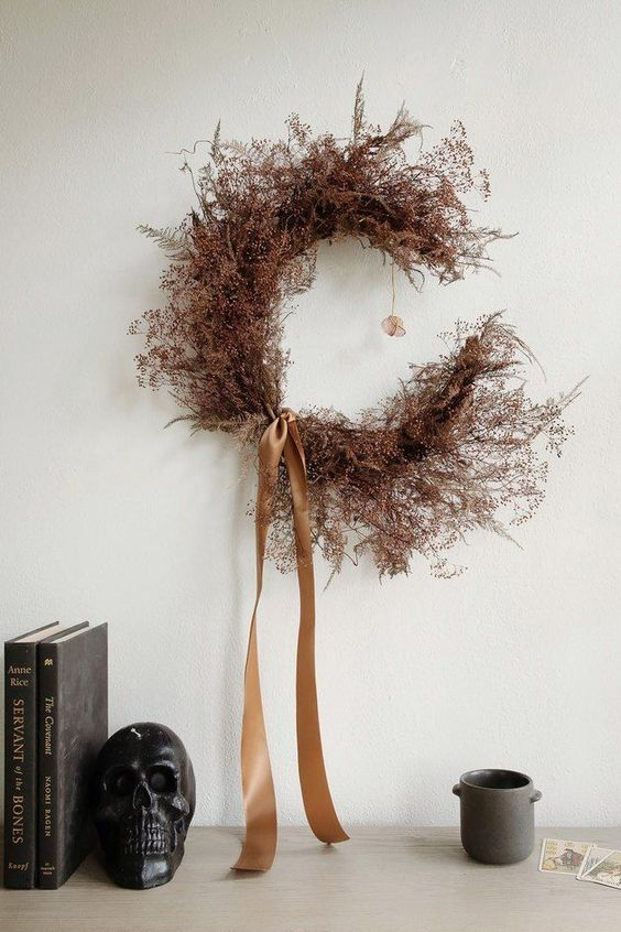 a moody dried flower and herb crescent moon Halloween wreath with tan silk ribbon is a stylish idea for the fall, too
