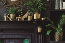 a moody living room with black walls and built-in shelves, a built-in black fireplace, green tiles, brass planters and pots and greenery in them plus a sunburst brass mirror