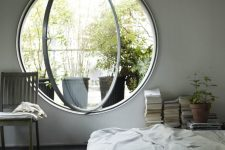 a neutral and airy bedroom done with a round pivot window, which allows fresh air in easily and brings much light