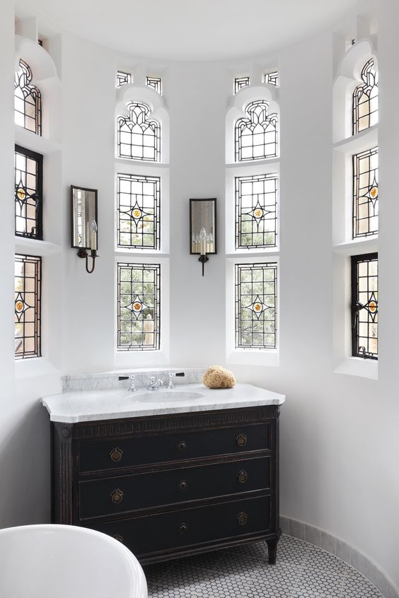 a neutral bathroom with small window with stained glass, a black vintage vanity, mirrors with lights and a tub is very chic