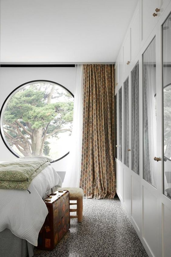 a cozy neutral bedroom design with a round window
