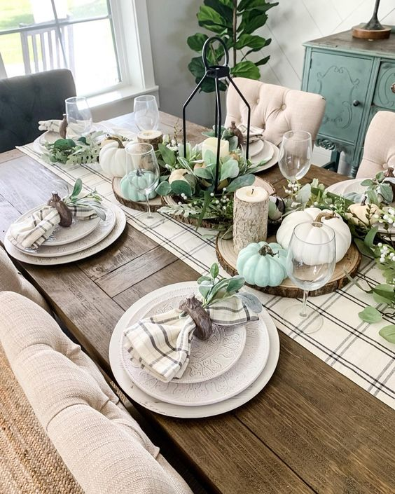 a neutral farmhouse Thanksgiving tablescape with a plaid runner and napkins, neutral and pastel pumpkins, candles and greenery is amazing