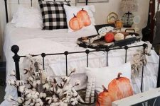 a neutral farmhouse bedroom with a gallery wall of empty frames, a forged bed, neutral and plaid bedding,a shabby chic bench, pumpkin pillows and cotton in a basket