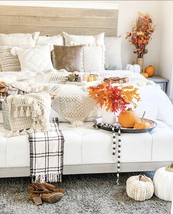 a neutral farmhouse bedroom with a stained bed, neutral fluffy bedding, a white upholstered bed, faux and knit pumpkins and lots of fall leaves
