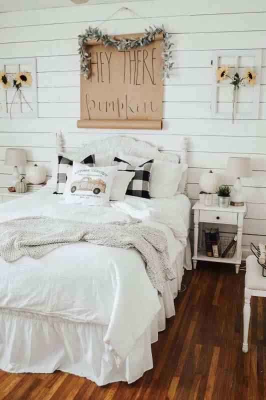 a neutral farmhouse bedroom with planked walls, a refined white bed and nightstands, neutral and plaid bedding, sunflowers, greenery and faux pumpkins