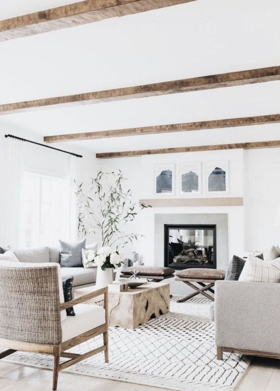a neutral farmhouse living room with wooden beams, a large built-in fireplace, neutral seating furniture, a wooden slab table and greenery