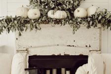a neutral farmhouse mantel with lush greenery, white pumpkins, a vine wreath with eucalyptus, pillar candles right in the fireplace