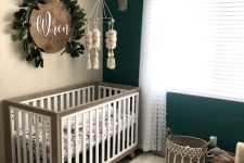 a neutral farmhouse nursery with an emerald planked accent wall, neutral crib, baskets for storage, a wooden bead chandelier and a sign