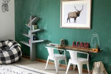 a stylish kids room with a large green chalkboard wall