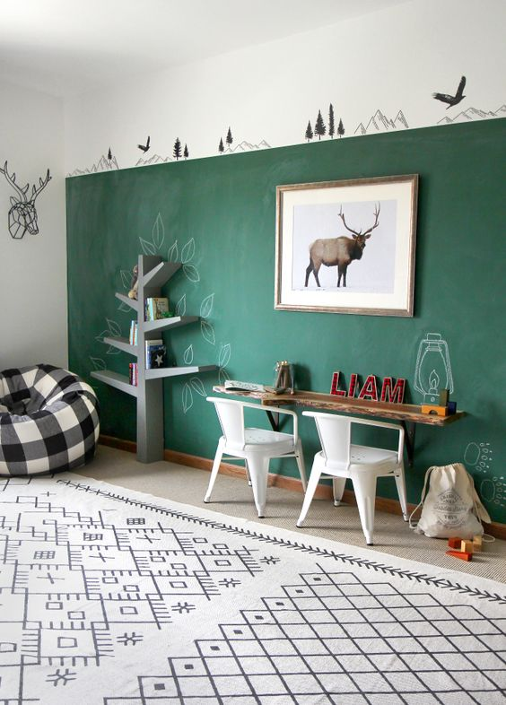 a neutral playroom accented with a green chalkboard wall, a floating desk and chairs, a tree shelving unit and a printed rug and a pouf