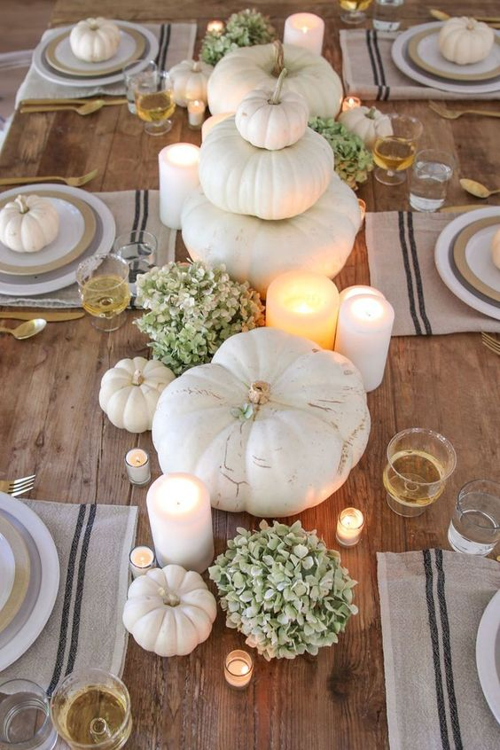 a neutral rustic Thanksgiving tablescape with an uncovered table, striped placemats, heirloom pumpkins, green hydrangeas and candles