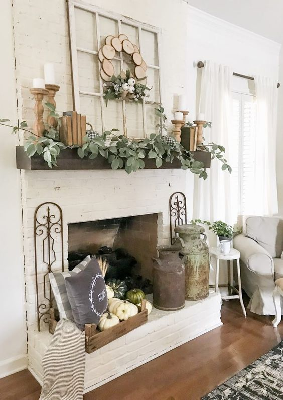a neutral rustic mantel with greenery, books, wooden candleholders, a wood slice wreath, a tray with pumpkins and vintage churns