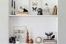 a niche with shelves and Halloween decor – a patterned pumpkin, a skull in a cloche, a black skull, a skeleton bird and black candles