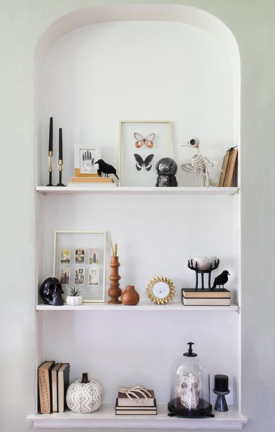 a niche with shelves and Halloween decor   a patterned pumpkin, a skull in a cloche, a black skull, a skeleton bird and black candles