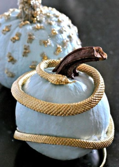 a pale blue pumpkin wrapped with a gold snake is a stylish and refined idea for your Halloween decor