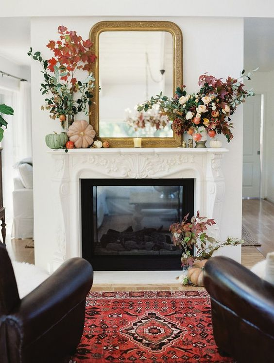 a pretty and bold fall mantel with bright and pastel pumpkins, a mirror in an ornated frame, bold leaves and blooms is a very chic idea