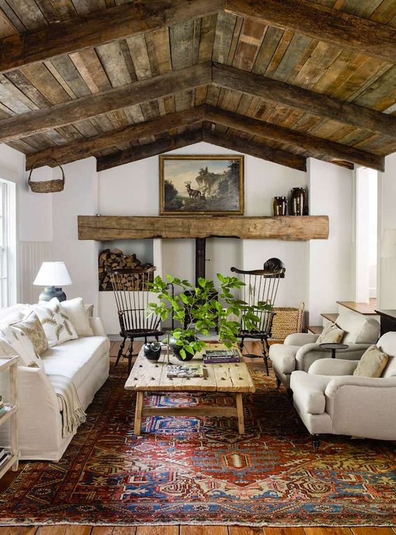 a pretty and bold living room with a reclaimed wood ceiling and wooden beams, a hearth and firewood, neutral seating furniture, a wooden table and a printed rug