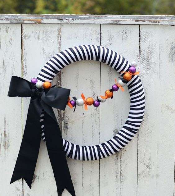 a pretty black and white striped Halloween wreath with a colorful ornament garland and a black ribbon bow is an out of the box idea
