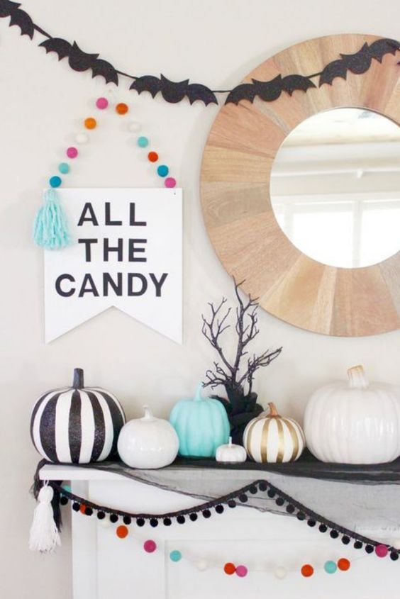 a pretty colorful modern fireplace with pompom garlands, black bat buntings, white and black pumpkins, a sign is all cool