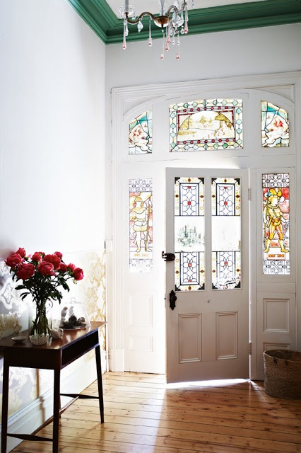 a pretty entry with a stained glass door and sidelights, with modern furntiure and a crystal chandelier plus bold blooms