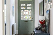 a pretty entryway with a green door with stained glass, a gallery wall, a black vanity with some art and pendant lamps