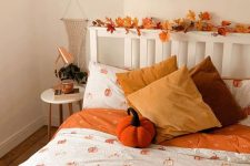 a pretty fall bedroom with a fall leaf garland interweaving the headboard, bright orange pumpkin bedding and mustard pillows, copper lamps