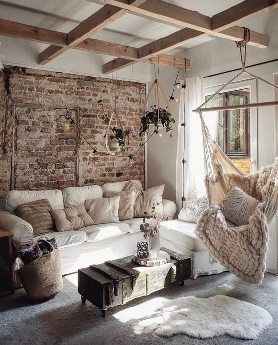 a pretty farmhouse living room with wooden beams, white seating furniture, a pendant chair, lights and an industrial coffee table