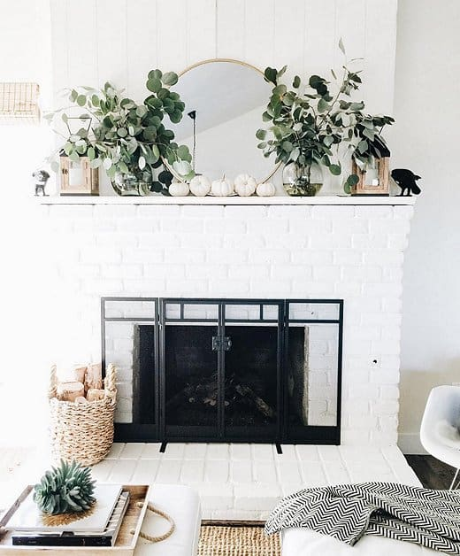 a pretty farmhouse mantel with white pumpkins, eucalyptus in vases, wooden candleholders and a blackbird is cool and fresh