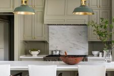 a pretty green kitchen with shaker cabinets, a white stone backsplash and countertops, white stools, green and brass pendant lamps and brass fixtures
